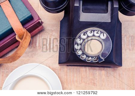 High angle view of old landline telephone with diaries and coffee on table