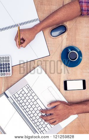 Overhead view of businessman writing on book while working on laptop in office