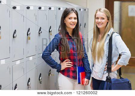 Smiling students posing near locker at university