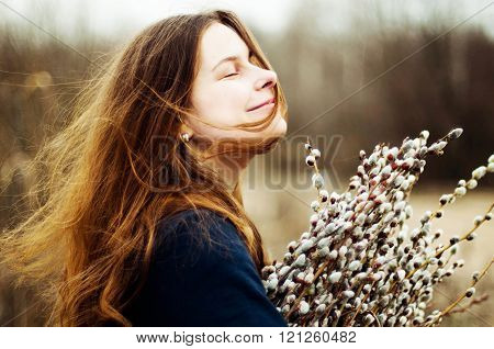 Portrait of a beautiful young girl with a huge armful of willow in hands. Young woman gardening. Portrait of a girl in nature. Girl with willow outdoors.