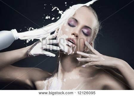 Portrait of a beautiful blonde dousing with cream