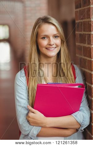 Smiling student with binder posing in the hallway
