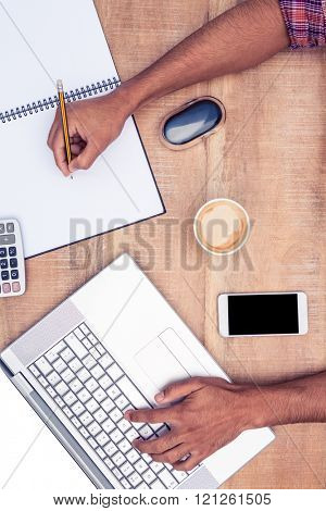 Overhead view of businessman working on laptop while writing on book at desk in office