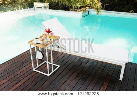 Tray with breakfast in side table and sun lounger near poolside