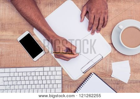 Cropped image of businessman writing on notebook by computer keyboard at desk in office