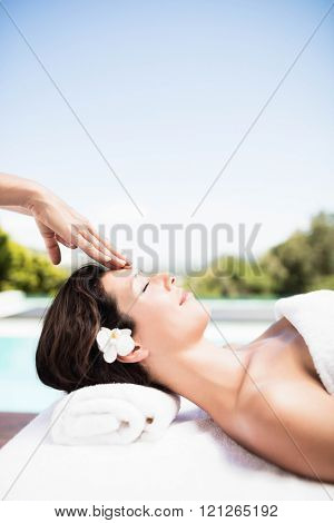 Woman receiving a head massage from masseur in a spa
