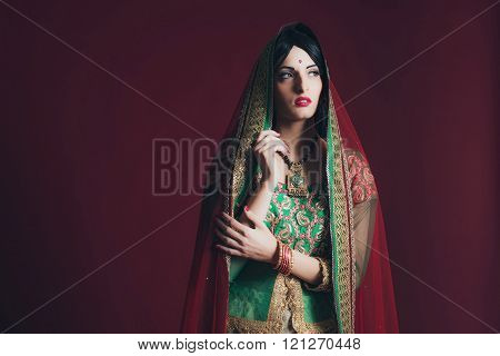 Vintage Bollywood Fashion Girl Against Dark Red Background.