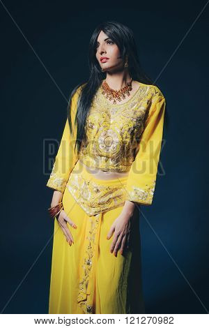 Vintage Bollywood Fashion Girl In Yellow Clothes Against Dark Blue Background.