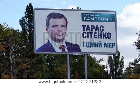 KHARKOV, UKRAINE - CIRCA OCTOBER 2015: Held high billboard with a portrait of the candidate in mayors close-up on background of autumn trees and autumn sky.
