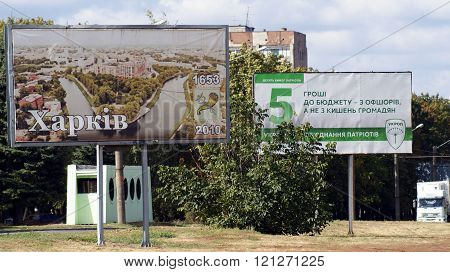 KHARKOV, UKRAINE - CIRCA OCTOBER 2015: Billboard with views of the city and coat of arms of Kharkov and a billboard of association UKROP (DILL) with the basic aspirations of voters by road on the background of the wasteland,  autumn sky and autumn trees.