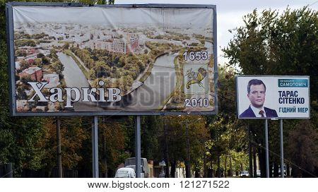KHARKOV, UKRAINE - CIRCA OCTOBER 2015: A billboard with a portrait of the candidate in mayors and the billboard with views of Kharkiv on the background of the square near the road. Depicts the coat of arms of Kharkov and the year of foundation of the city