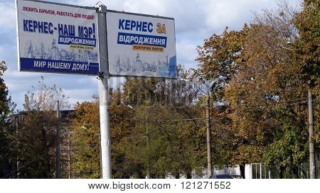 KHARKOV, UKRAINE - CIRCA OCTOBER 2015: Two billboards of the one mayoral candidate depicting historical places of Kharkov next to each other on the background of the autumn sky and autumn trees.