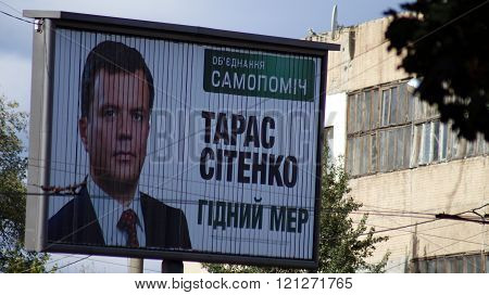 KHARKOV, UKRAINE - CIRCA OCTOBER 2015: A billboard with a portrait of the candidate in mayors close-up in the grid of a wires on the background of an abandoned workshop.