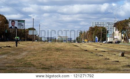 KHARKOV, UKRAINE - CIRCA OCTOBER 2015: A billboard with a portrait of the candidate in mayors close-up at the sight of the city, autumn sky and autumn trees. In the foreground a man carrying a Bicycle wheel.
