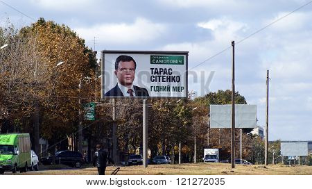 KHARKOV, UKRAINE - CIRCA OCTOBER 2015: A billboard with a portrait of the candidate in mayors close up near the road on the background of the autumn sky and autumn trees. In the foreground a man carrying a bicycle wheel.