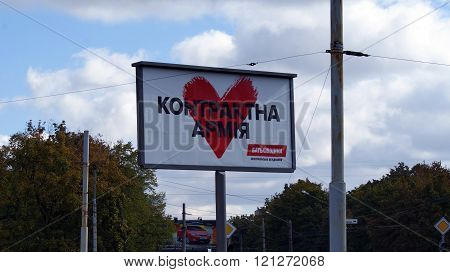 KHARKOV, UKRAINE - CIRCA OCTOBER 2015: Billboard on the background of urban development. A billboard with a picture of a big red heart on the background of the autumn sky and autumn trees.