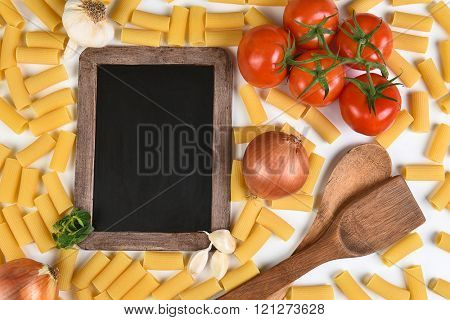 Top view of a blank chalkboard with the ingredients for an Italian meal. Horizontal format.