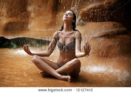 Young woman doing yoga exercise under waterfall