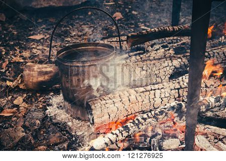 Cast iron pot outdoors, cooking on a fire.