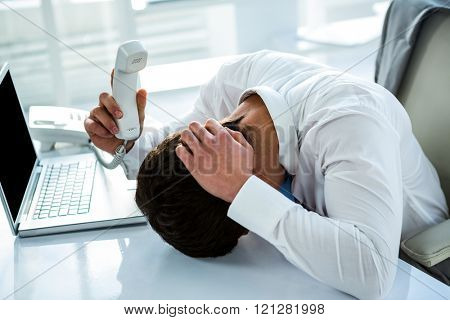 Overwhelmed asian businessman answering the phone in office