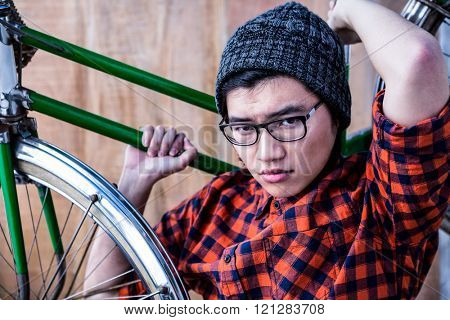 Hipster carrying a bike on his shoulders on wooden background