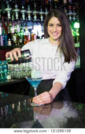 Pretty bartender pouring a blue martini drink in the glass at bar