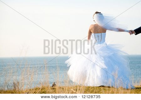 Bride in wedding dress staying at field and looking into sea outdoors