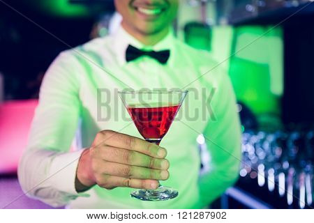 Bartender serving glass of cocktail at bar counter in bar