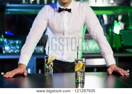 Two glasses of gin on bar counter and bartender leaning in background