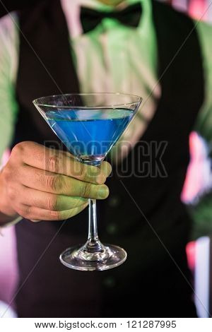 Close-up of bartender serving glass of cocktail at bar counter in bar