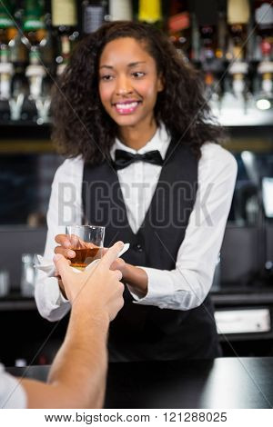 Female barmaid serving a glass of whiskey in bar