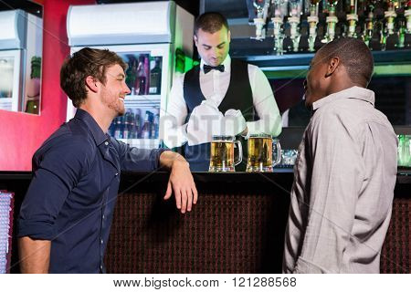 Two men smiling and talking to each other while having beer at bar counter in bar
