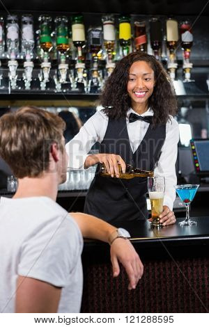 Beautiful barmaid pouring beer in glass at bar counter in bar