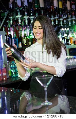 Pretty bartender mixing a cocktail drink in cocktail shaker at bar