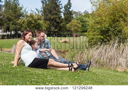 Young Pregnant Family Relaxing In The Park