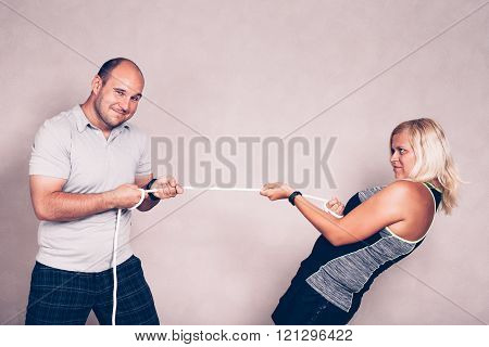 Confident Man And Woman Pulling A Rope