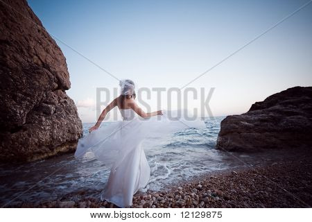 Fashion bride posing on beach with wedding dress in motion