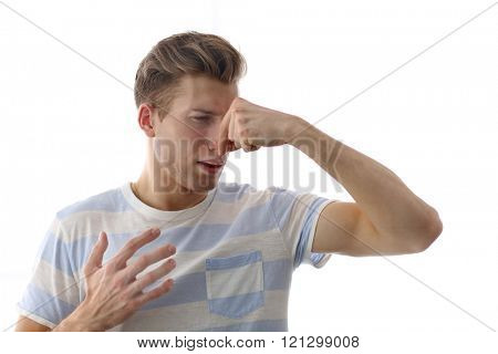 Young blonde man pinching his nose because of the stench, isolated on white