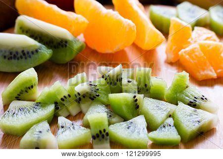 Sliced Kiwi On A Background Of Orange Slices Closeup