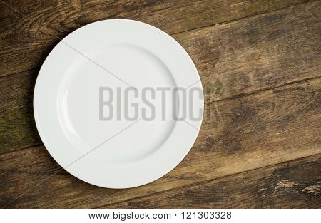 Empty white plate on rustic wooden background