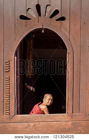 NLE,MYANMAR-Novemberl 24 : Young novice monk at window wooden Church of Nyan Shwe Kgua temple near Inle lake on November 24,2015 in Inle lake,Shan State ,Middle of Myanmar.