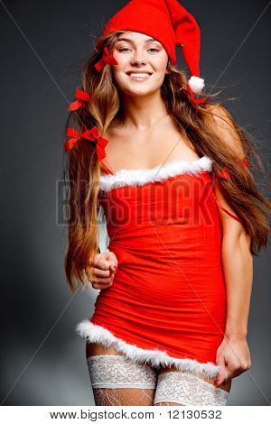 Sexy santa helper girl with long beautiful hair wearing stocking posing on gray studio background