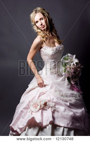 Beautiful blond bride wearing wedding dress posing on gray studio background