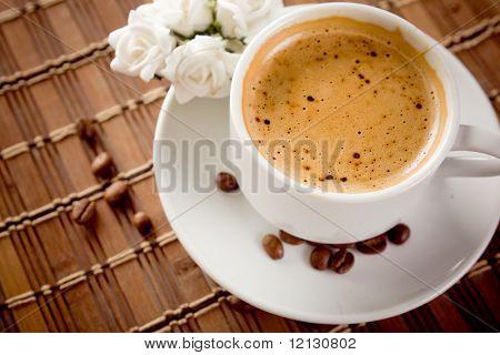 Café en mesa con escasas frijoles, enfoque en el líquido de la mañana.