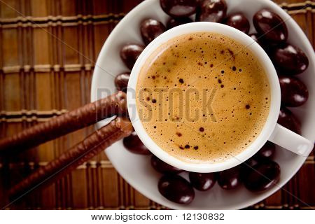 Cup of coffee on a table with chocolate nuts and sticks