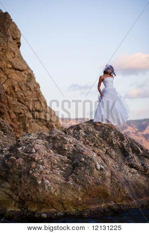 Bride in fashion wedding dress posing on mountain over sea