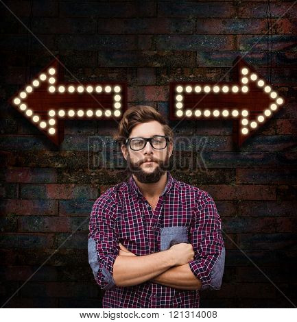 Confident hipster wearing eye glasses with arms crossed against brick wall