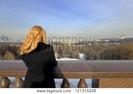The girl looks at the panorama of the city