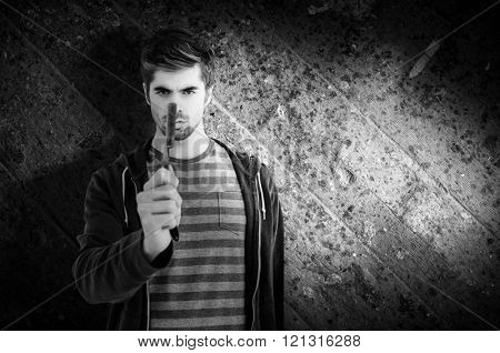 Portrait of man holding straight edge razor against wooden floor
