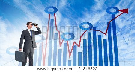 Businessman looking through binoculars against blue data